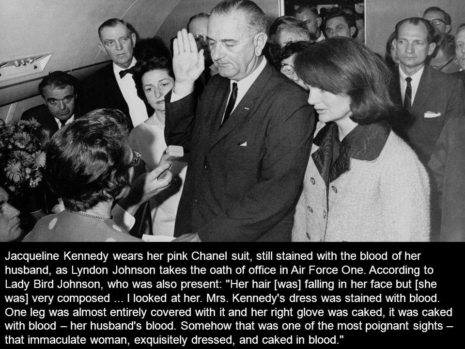 Jacqueline Kennedy wears her pink Chanel suit, still stained with the blood of her husband, as Lyndon Johnson takes the oath of office in Air Force One. According to Lady Bird Johnson, who was also present: Her hair [was] falling in her face but [she was] very composed ... I looked at her. Mrs. Kennedy s dress was stained with blood.